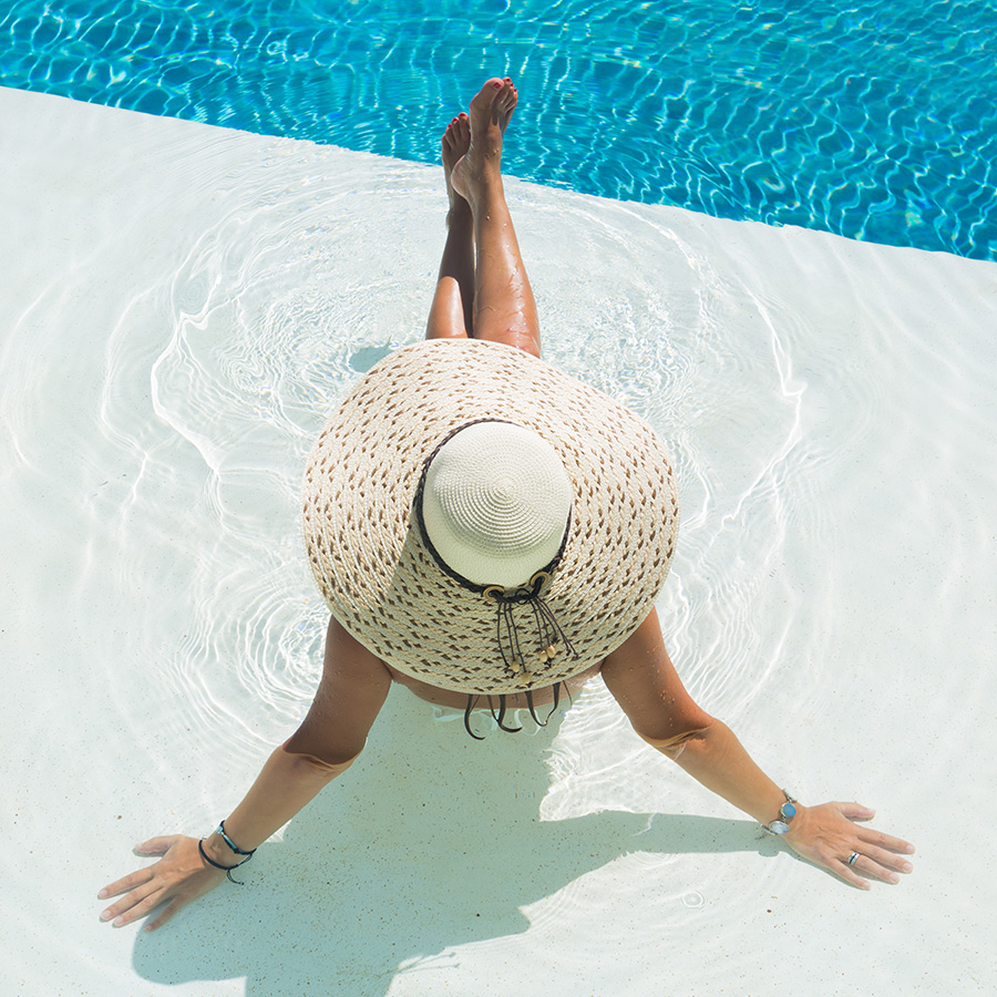 Woman in Pool Wearing Hat Preventing Sun Damage