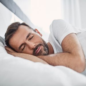 man sleeping in bed getting a better sleep