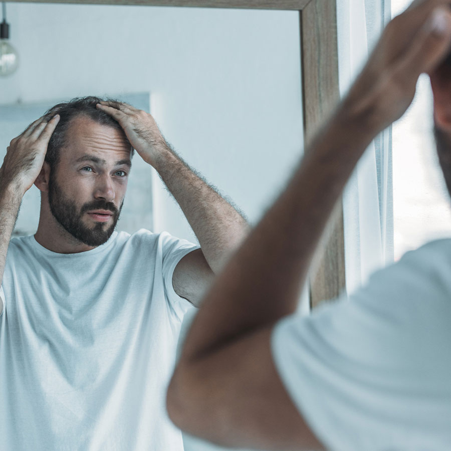 man looking in mirror combing hair with hands
