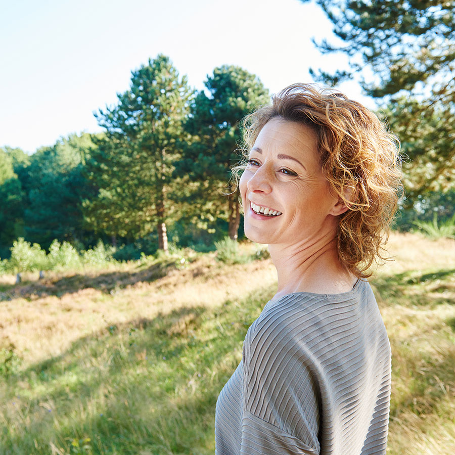 woman smiling standing in nature hormone balance